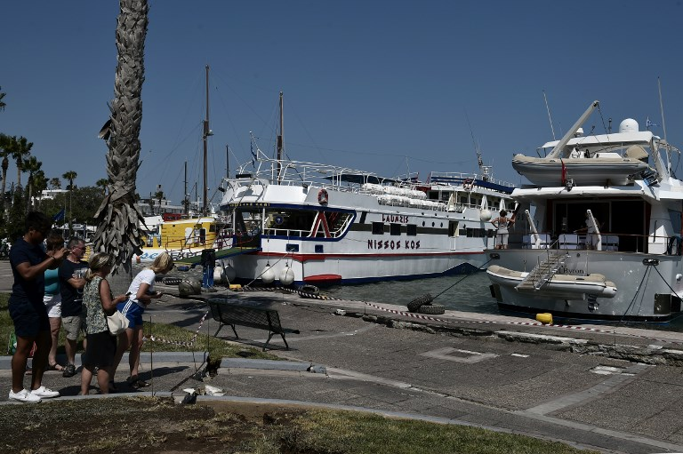 Les touristes regardent un quai endommagé sur l'île grecque de Kos, le 21 juillet 2017, après un séisme d'une magnitude de 6,5 qui a frappé la région (Crédit : LOUISA GOULIAMAKI/AFP PHOTO)