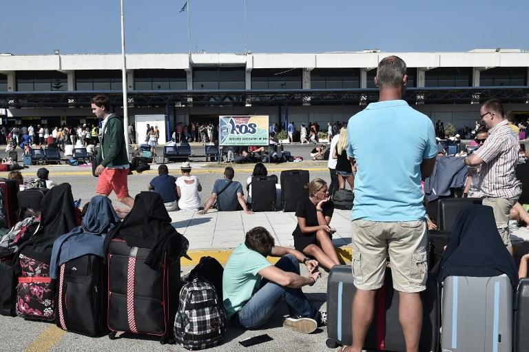 Des touristes attendent devant le Terminal de l'aéroport de l'île grecque de Kos, le 21 juillet 2017, suite à un séisme d'une magnitude de 6,5 qui a touché la région (Crédit : LOUISA GOULIAMAKI/AFP PHOTO)