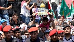 Les Jordaniens portent une maquette de la mosquée du Dôme du Rocher lors d'une manifestation, appelée par le Front d'action islamique, à Amman après les prières de vendredi le 21 juillet 2017, pour protester contre les nouvelles mesures de sécurité israéliennes mises en œuvre sur le site sacré, qui comprennent des détecteurs de métaux et des caméras (Crédit : AFP / Khalil MAZRAAWI)