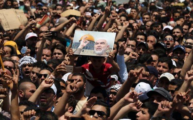 Les Jordaniens portent un portrait du sheikh Raed Salah, le chef de l'aile du nord du Mouvement islamique en Israël, lors d'une manifestation, appelée par le Front d'action islamique, à Amman après les prières du vendredi le 21 juillet , 2017, pour protester contre les nouvelles mesures de sécurité israéliennes mises en œuvre sur le site sacré, qui comprennent des détecteurs de métaux et des caméras, Amman, Jordanie (Crédit : AFP PHOTO / Khalil MAZRAAWI