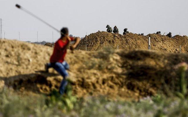 Un manifestant envoie une pierre aux troupes israéliennes durant des affrontements survenus à proximité de la barrière de sécurité de Gaza, à l'est du camp de réfugiés de Jabalia, le 21 juillet  2017, en protestation contre les nouvelles mesures de sécurité israéliennes sur le mont du Temple à Jérusalem (Crédit : AFP / MOHAMMED ABED)