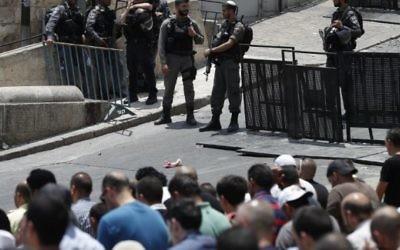 Les forces de sécurité israéliennes surveillent les fidèles musulmans palestiniens qui prient à l'extérieur de la Porte des Lions, une entrée principale du mont de Tempe dans la Vieille Ville de Jérusalem, le 22 juillet 2017. (Crédit : AFP / Ahmad Gharabli)