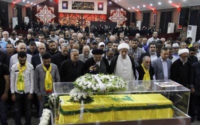 Des religieux et des membres du Hezbollah se recueillent sur le cercueil d'un médiateur tué à Jouroud Arsal, à la frontière syrienne, le 23 juillet 2017. (Crédit : AFP PHOTO / STRINGER)