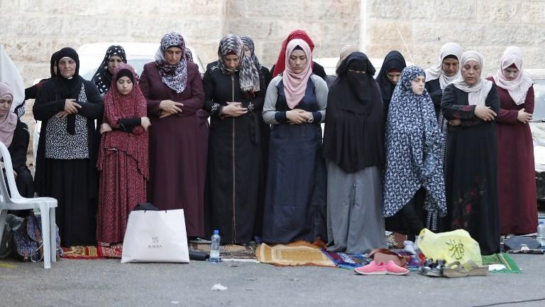 Des musulmanes prient hors de la Vieille ville de Jérusalem le 25 juillet 2017 (Crédit : AFP Photo/Ahmad Gharabli/AFP Photo)