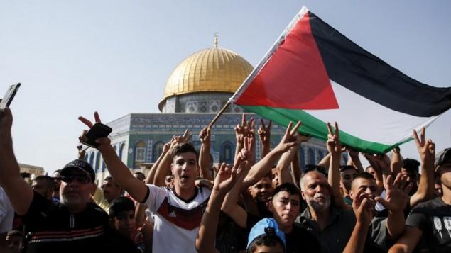 Les fidèles musulmans brandissent un drapeau palestinien devant le Dôme du Rocher sur le mont du Temple, le 27 juillet 2017 (Crédit : AFP Photo / Ahmad Gharabli)