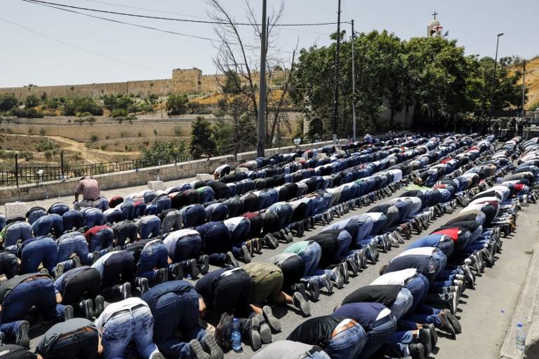Les fidèles musulmans prient en dehors de la Vieille Ville de Jérusalem près de la Porte des Lions le 28 juillet 2017 (Crédit : AFP / Menahem Kahana)