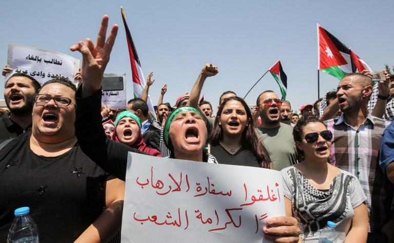 Des manifestants jordaniens brandissent des drapeaux nationaux et scandent des slogans durant une manifestation à proximité de l'ambassade israélienne dans la capitale d'Amman, le 28 juillet 2017, appelant à la fermeture de l'ambassade, au renvoi de l'ambassadeur et à l'annulation du traité de paix de 1994 avec Israël. (Crédit : KHALIL MAZRAAWI/AFP)