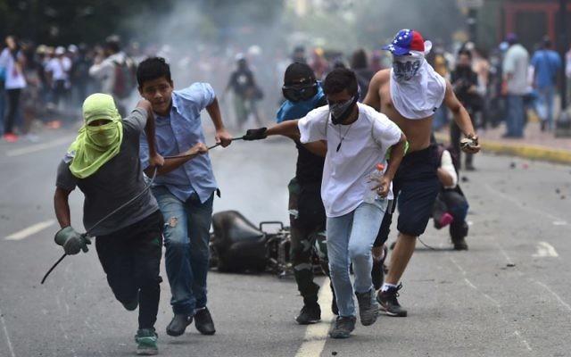 Les militants anti-gouvernementistes font glisser une moto de police brûlée après l'explosion d'un engin explosif lors d'une manifestation contre les élections d'une assemblée constituante à Caracas le 30 juillet 2017. (Crédit : AFP / Ronaldo SCHEMIDT)