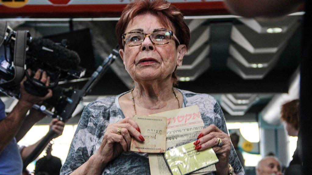 Une survivante de l'Exodus montre des documents de voyage, au port de Haifa, le 18 juillet 2017 (Crédit : Laura Ben-David)