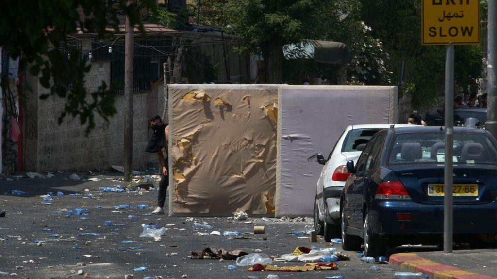 Les émeutiers de Jérusalem-Est se cachent derrière des matelas pour bloquer les balles en caoutchouc tirées par la police au cours d'agitations survenues dans le quartier Wadi Joz le 21 juillet 2017 (Crédit : Micah Danney/Times of Israel)