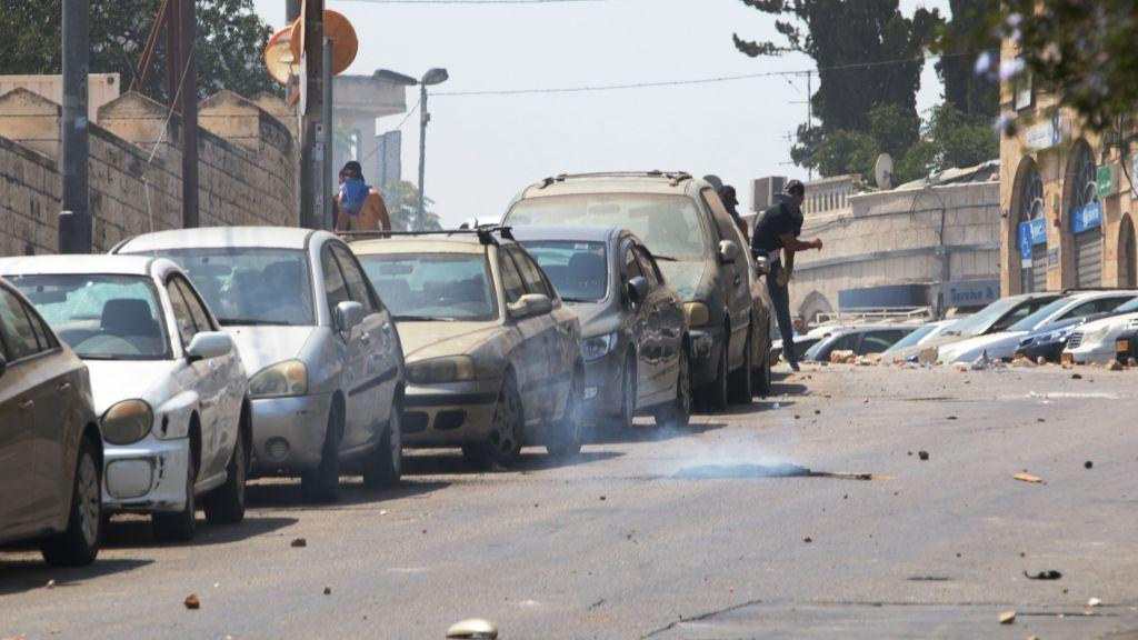 Des émeutiers masqués jettent des pierres sur la police au cours d'une émeute survenue dans le quartier de Wadi Joz le 21 juillet 2017 (Crédit : Micah Danney/Times of Israel)
