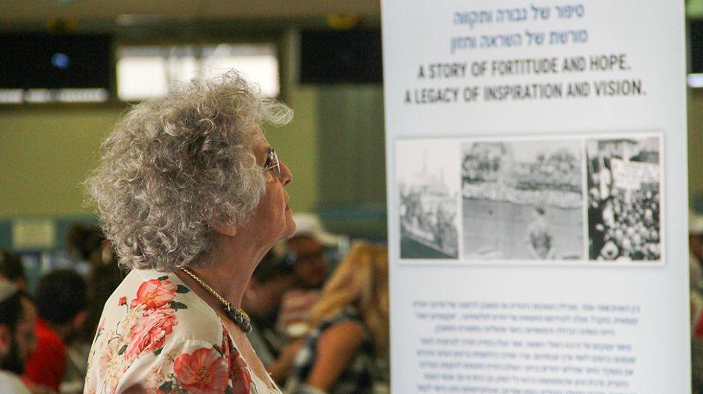 Une survivante de l'Exodus regarde l'exposition commémorative au port de Haifa, le 18 juillet 2017 (Crédit : Laura Ben-David)
