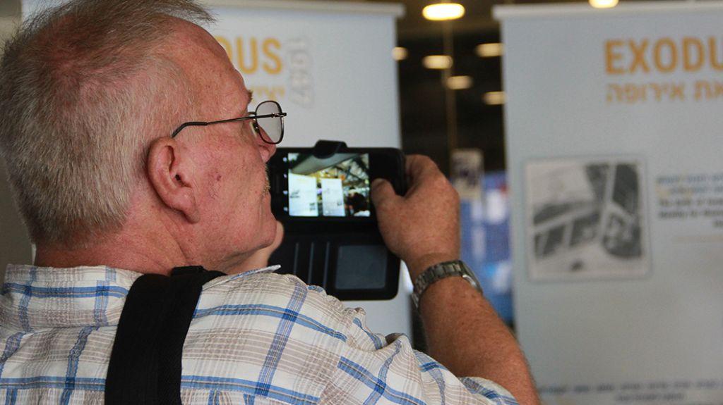 Un invité photographie l'exposition commémorative de lExodus au port de Haifa, le 18 juillet 2017 (Crédit : Laura Ben-David)