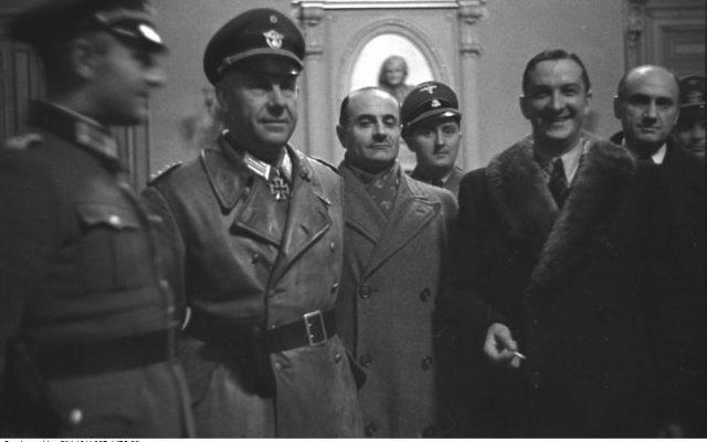 René Bousquet (avec col de fourrure, le 2e en partant de la droite) entouré par, de gauche à droite, le SS-Sturmbannführer Bernhard Griese (en manteau de cuir), le préfet régional Antoine Lemoine, le chef local de la Sipo et du SD Rolf Mühler (de) (derrière Lemoine), l'administrateur de Marseille Pierre BarraudN 6, à l'hôtel de ville de Marseille le 23 janvier 1943, pendant la rafle de Marseille (Crédit : CC BY-SA 3.0 de)