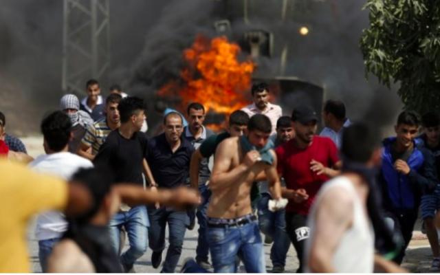 Les jeunes palestiniens lors des affrontements dans le village de Koubar, à l'ouest de Ramallah, le 22 juillet 2017, alors que les forces israéliennes tentent de fermer les routes menant au village. (Crédit : AFP / Abbas Momani)