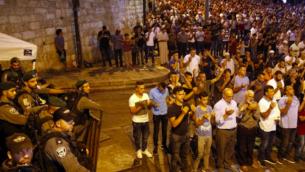 Les forces de sécurité israéliennes se tiennent aux côtés des fidèles musulmans palestiniens qui prient à l'extérieur de la Porte des Lions, près d'une entrée principale du mont du Temple dans la Vieille Ville de Jérusalem, le 24 juillet 2017. (Crédit : AFP / Ahmad GHARABLI)