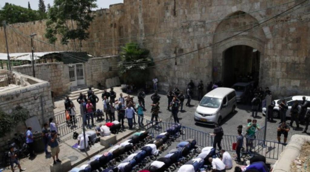 Les fidèles musulmans prient en dehors de la Porte des Lions de la Vieille Ville de Jérusalem aux entrées du Mont du Temple le 17 juillet 2017. (Crédit : AFP / Ahmad Gharabli)
