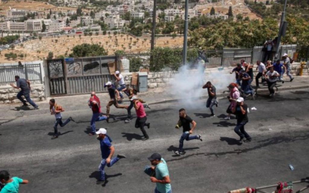 Des Palestiniens courent alors que la police israélienne émet des gaz lacrymogènes après les affrontements lors des prières du vendredi dans le quartier de Jérusalem-Est à Wadi al-Joz, le 28 juillet 2017 (Crédit : Miriam Alster / Flash90)