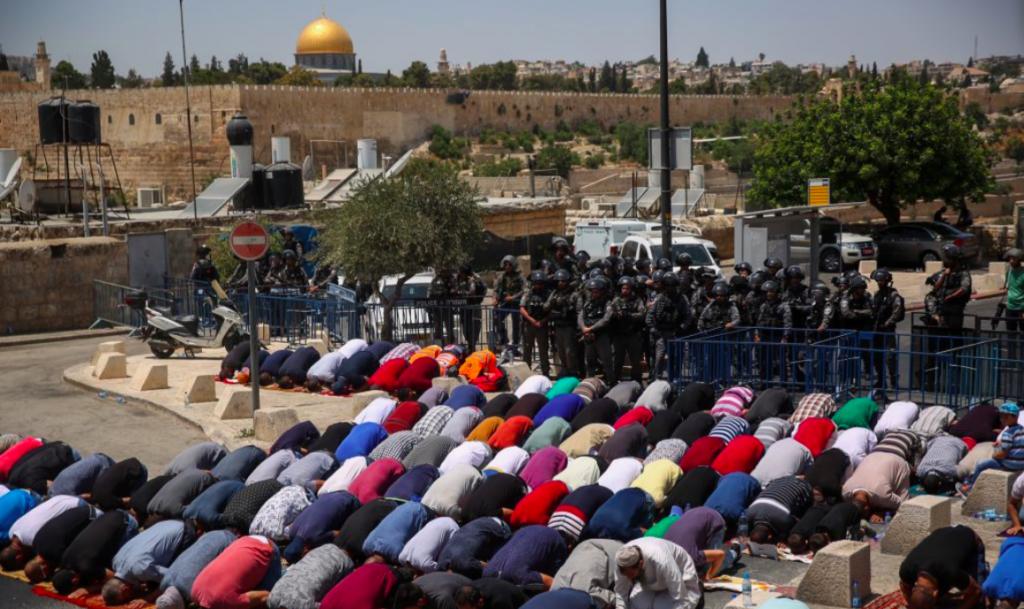 Les fidèles prient en dehors du mont du Temple sous l'oeil des forces de sécurité israéliennes, le 28 juillet 2017 (Crédit : Hadas Parush/Flash90)