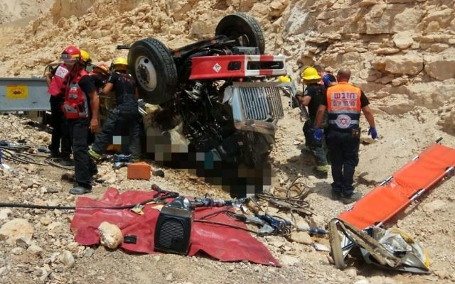 Secouristes et pompiers sur les lieux d'un accident qui a tué deux personnes, au nord d'Eilat, le 13 juillet 2017. (Crédit : Magen David Adom)