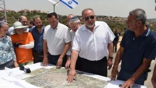 Le ministre de la Défense Avigdor Liberman présente son plan qui permettrait l'epansion de la ville de Qalqilya dans la zone actuellement contrôlée par Israël durant une visite dans l'implantation de Maale Shomron le 12 juillet 2017 (Crédit : Eden Moldavski/Defense Ministry)