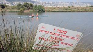 Photo illustrative de rameurs israéliens et un panneau d'avertissement mettant en garde contre l'eau polluée à l'extérieur de Haifa, le 18 mai 2013 (Crédit : Shay Levy / Flash 90)