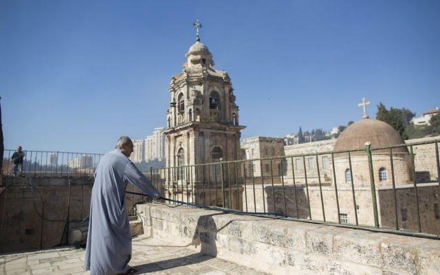 """Un moine orthodoxe du monastère de la Croix avec un tuyau, alors qu'il se tient sur le toit du monastère pendant un incendie survenu dans la """"Vallée de la croix"""", dans le centre de Jérusalem, le 2 juillet 2013 (Crédit : FLASH90)"""