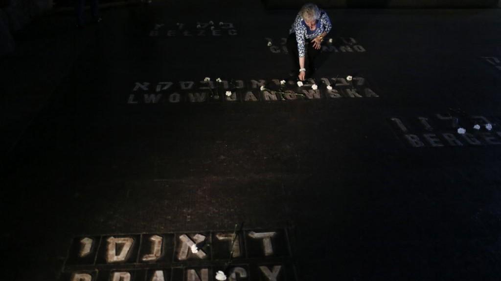 Des proches des survivants de la Shoah déposent des fleurs et des bougies sue les noms des camps de concentration, dans la Crypte du Souvenir, à Yad Vashem, à l'occasion de la Journée internationale de commémoration de la Shoah, le 28 avril 2014. (Crédit : Mriam Alster/Flash90)
