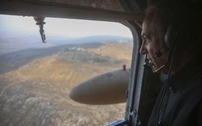 Le Premier ministre israélien Benjamin Netanyahu regarde la vue depuis un hélicoptère alors qu'il s'apprête à visiter la nouvelle barrière entre Israël et le territoire de Cisjordanie dans la zone de Tarqumiyah, le 20 juillet 2016 (Crédit :Marc Israel Sellem/POOL)