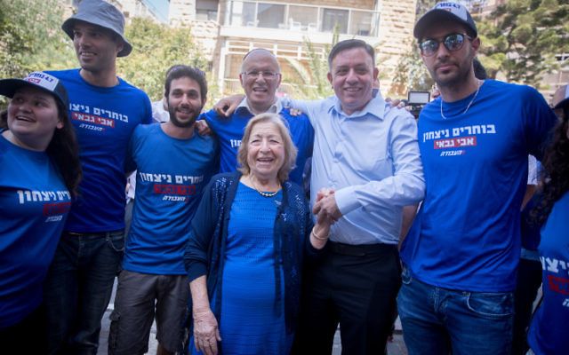 Avi Gabbay, en chemise, candidat à la tête du Parti travailliste, avec ses partisans devant un bureau de vote de Jérusalem, le 4 juillet 2017. (Crédit : Yonatan Sindel/Flash90)