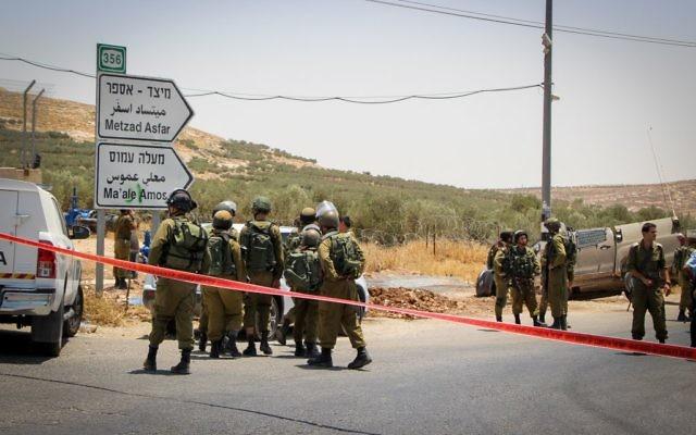 Des soldats sur le lieu d'un attaque à la voiture bélier dans le centre de la Cisjordanie, le 10 juillet 2017. (Crédit : Gershon Elinson/Flash90)