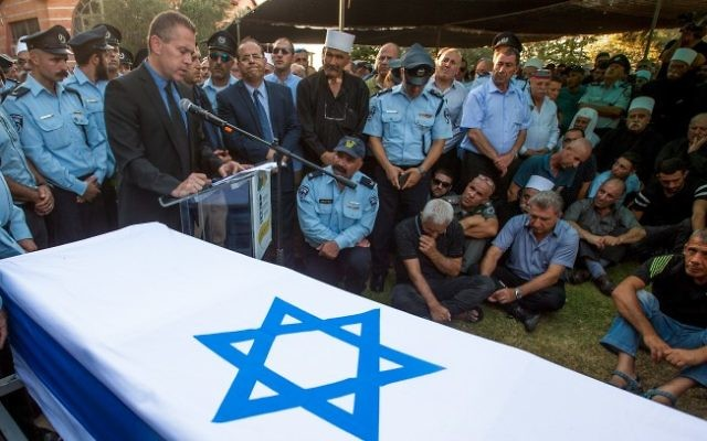 Le ministre israélien de la Sécurité intérieure Gilad Erdan parle durant les funérailles de l'agent de police druze israélien Kamil Shnaan dans le village de Hurfeish, dans le nord du pays. Les adjudants Kamil Shnaan Sitawe ont été assassinés  durant l'attentat terroriste commis aux abords du mont du Temple à Jérusalem, le 14 juillet 2017 (Crédit : Basel Awidat/Flash90).