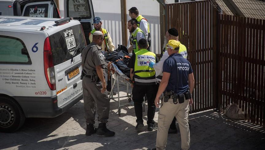 Le personnel médical israélien enlève le cadavre de l'un des terroristes impliqués dans un attentat à l'arme à feu à proximité du complexe du mont du Temple dans la Vieille ville de Jérusalem, le 14 juillet 2017 (Crédit : Hadas Parush/Flash90)