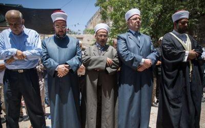 Des responsables du Waqf et des fidèles prêts à prier à l'extérieur du Mont du Temple plutôt que de passer par les détecteurs de métaux installés après un attentat, dans la Vieille Ville de Jérusalem, le 16 juillet 2017 (Crédit : Yonatan Sindel/Flash90)