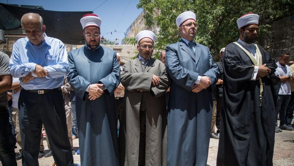 Des musulmans prient aux abords du mont du Temple dans la Vieille ville de Jérusalem, le 16 juillet 2017 (Crédit : Yonatan Sindel/Flash90)