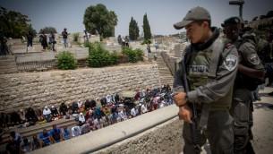 Les fidèles musulmans faisant les prières de midi par la Porte du Lion, en dehors du mont du Temple, dans la Vieille Ville de Jérusalem, le 20 juillet 2017 (Crédit : Miriam Alster / Flash90)