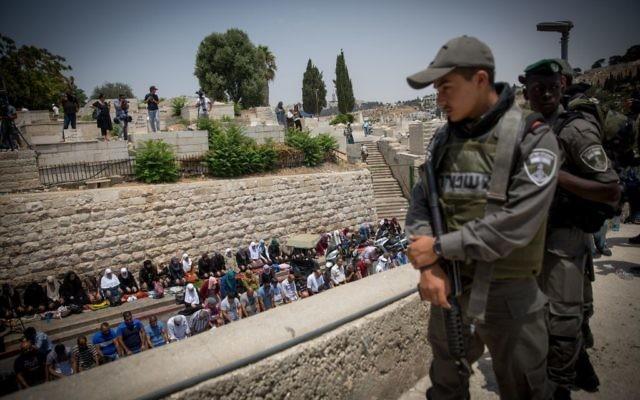Des fidèles musulmans prient devant la porte des Lions, à l'entrée du mont du Temple, dans la Vieille Ville de Jérusalem, le 20 juillet 2017. (Crédit : Miriam Alster)