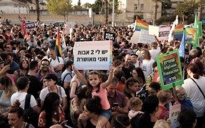 """Une petite fille brandit un panneau """"J'ai deux papas et je suis heureuse"""" alors que des milliers de personnes manifestent pour le droit des couples LGBT à adopter, à Tel Aviv, le 20 juillet 2017. (Crédit : Tomer Neuberg/Flash90)"""