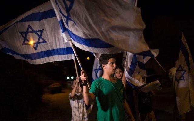 Des adolescents juifs israéliens brandissent des drapeaux israéliens aux abords de la maison de la famille Salomon dans l'implantation juive de  Halamish dans le nord de la Cisjordanie le 220 juillet 2017 (Crédit :  Hadas Parush/FLASH90)