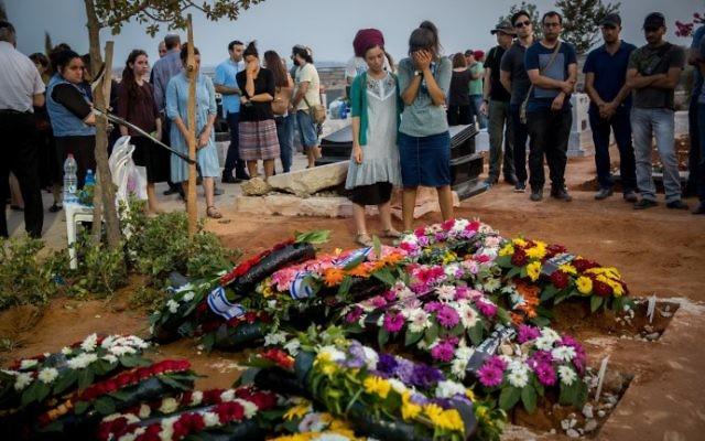 Des amis et des proches se recueillent sur la tombe de Yosef Salomon, 70 ans, sa fille Haya, 46 ans, et son fils Elad, 36 ans, après leurs funérailles qui ont réuni des milliers de personnes au cimetière de Modiin, le 23 juillet 2017 (Crédit : Yonatan Sindel/ FLASH90)