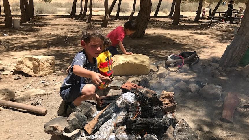 Un petit garçon devant un feu à Mitzpe Ramon, le 13 juin 2017. (Crédit : Andrew Tobin)