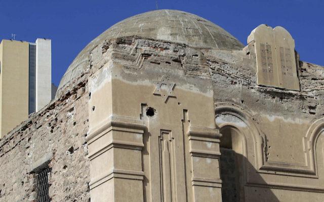 Un hôtel peut être aperçu derrière la synagogue abandonnée de  Dar Bishi à Tripoli,  en Libye le 28 septembre 2011 (Crédit : Joseph Eid/AFP/Getty Images/via JTA)