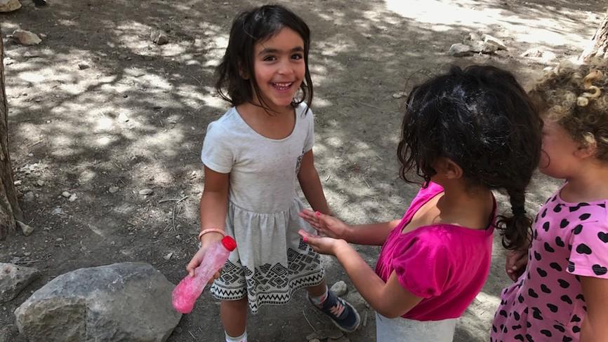 Une petite fille aide ses camarades à se laver les mains à Mitzpe Ramon, le 13 juin 2017. (Crédit : Andrew Tobin)