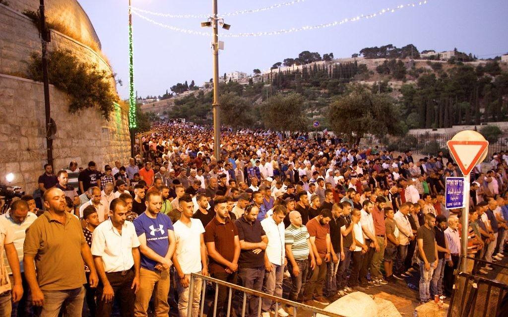 Des centaines de musulmans prient devant la porte des Lions dans la Vieille ville de Jérusalem, refusant d'entrer sur le mont du Temple, le 25 juillet 2017. (Crédit : Dov Lieber /Times of Israel)