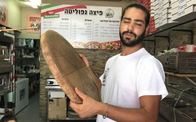 Shlomi Madar avec un plateau à pizza en bois, similaire à celui qu'il a employé pour neutraliser un terroriste palestinien qui a tenté de le poignarder dans sa pizzeria, à Petah Tikva, le 24 juillet 2017. (Crédit : Jacob Magid)