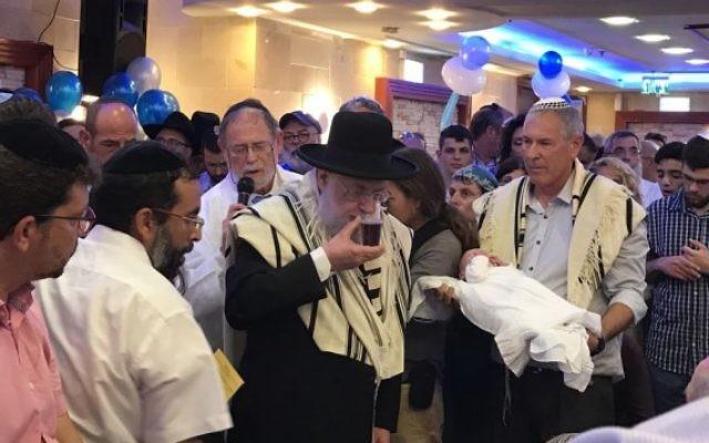 Les membres de la famille Salomon assistent à la circoncision de leur fils, Ari Yosef, dans la ville centrale d'Elad d'Israël, le 27 juillet 2017. (Crédit : Jacob Magid / Times of Israel)