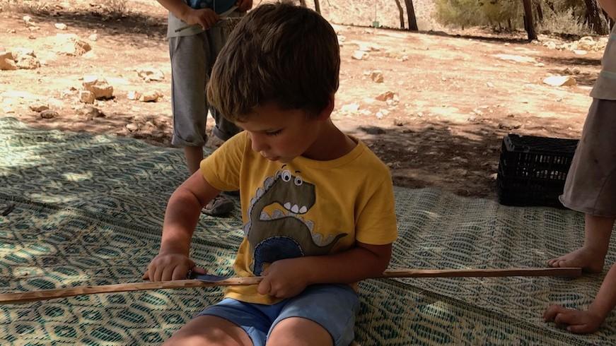 Un petit garçon sculpte un bâton avec un couteau à Mitzpe Ramon, le 13 juin 2017. (Crédit : Andrew Tobin)