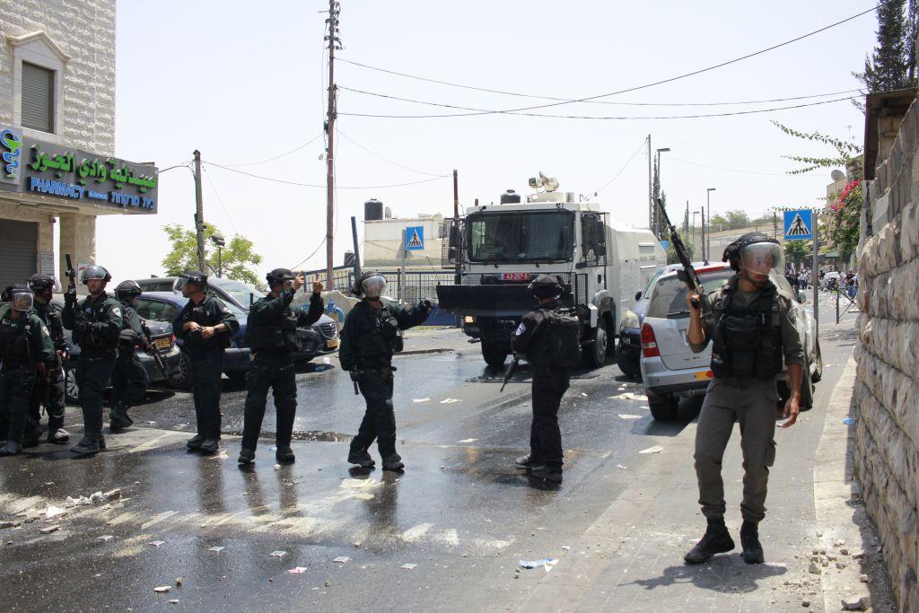 Des gardes-frontières et des agents de police, ainsi qu'un canon à eau, avancent dans le quartier de Wadi Joz durant une émeute là-bas le 21 juillet 2017 (Crédit : Judah Ari Gross/Times of Israel)