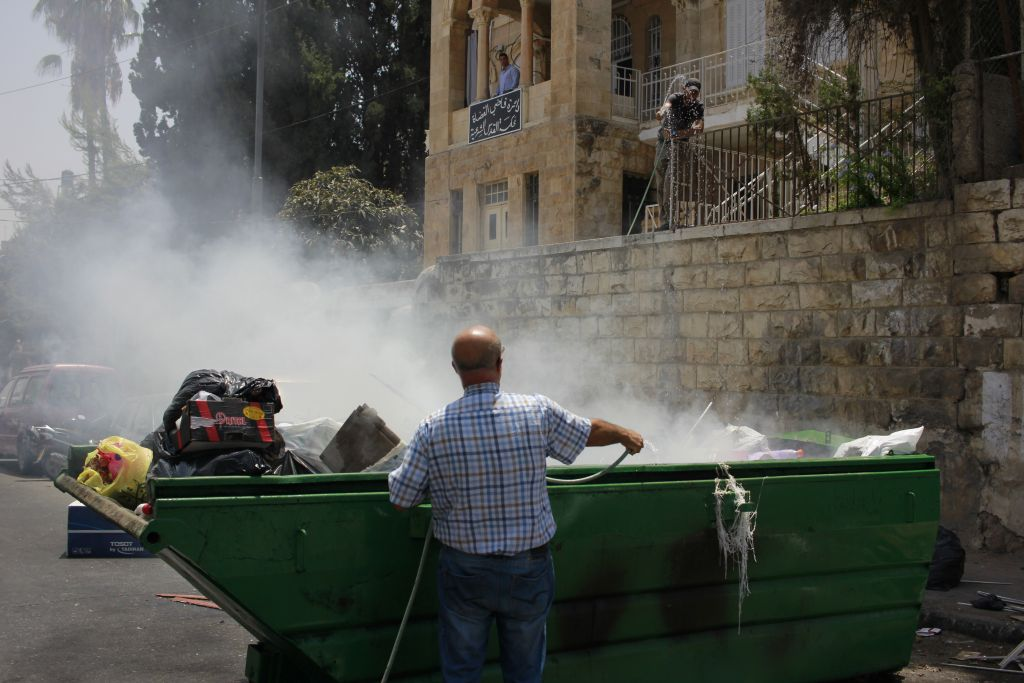 Les résidents éteignent un feu allumé dans une benne à ordures au cours d'une émeute dans le quartier de Wadi Joz, le 21 juillet 2017 (Crédit : Judah Ari Gross/Times of Israel)