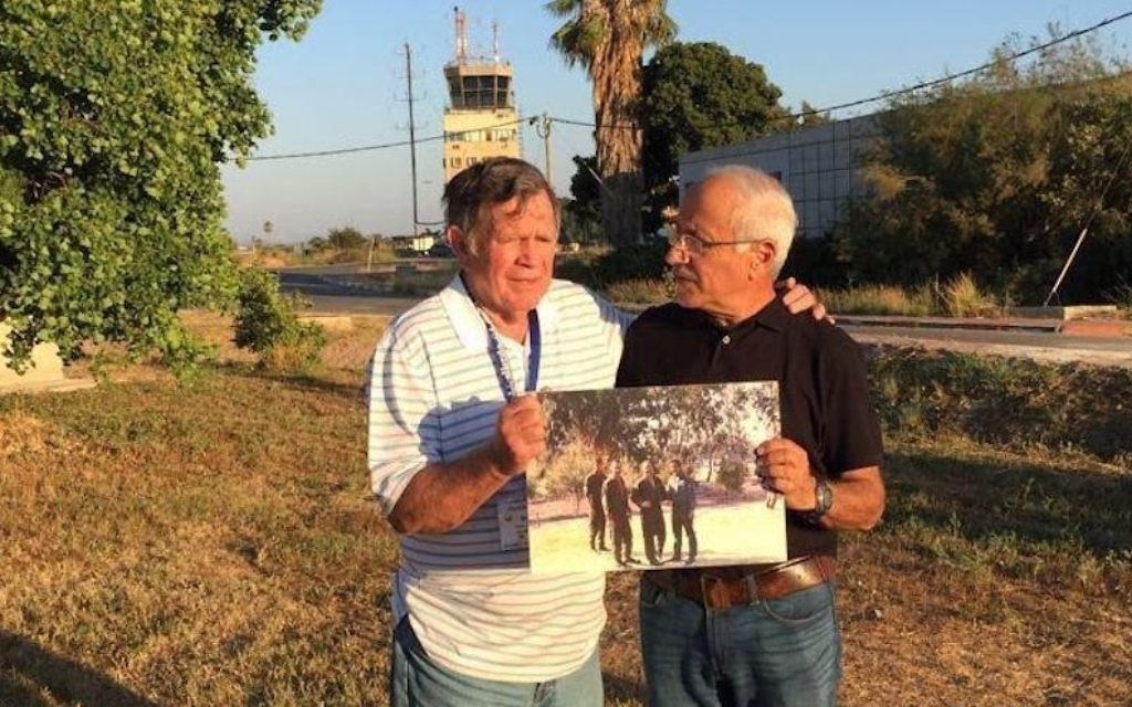 """Roy """"Bubba"""" Segars, pilote américain à la retraite, et le pilote de chasse israélien à la retraite Jacob """"Booby"""" Daube montrent une photo d'eux prise durant la guerre de Kippour en 1973, sur la même base de Tel Nof en Israël, le  28 juin 2017. (Crédit : unité du porte-parole de l'armée)"""